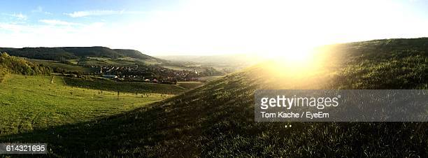 Scenic View Of Green Landscape Against Sky On Sunny Day