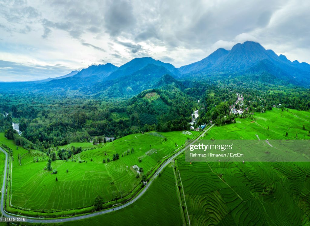 Scenic View Of Green Landscape And Mountains Against Sky : Stock Photo