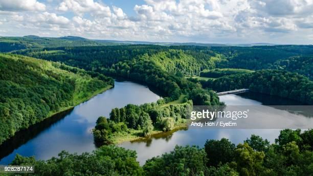 scenic view of green landscape and river against sky - fluss stock-fotos und bilder