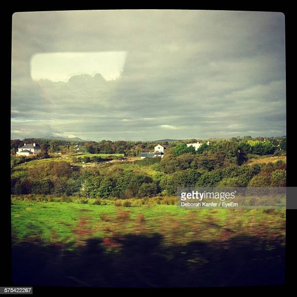 Scenic View Of Green Landscape Seen Through Train Window Against Sky