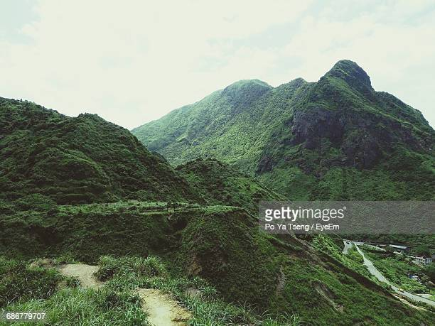 scenic view of green mountains against sky - poya day stock pictures, royalty-free photos & images