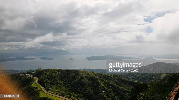 scenic view of green mountains by taal lake against cloudy sky - taal foto e immagini stock