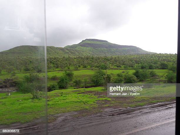 Scenic View Of Green Mountains Seen Through Bus Window