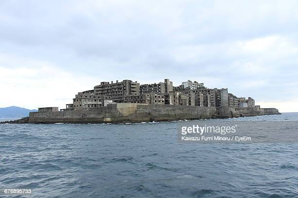 scenic view of hashima island against cloudy sky - nagasaki prefecture stock pictures, royalty-free photos & images