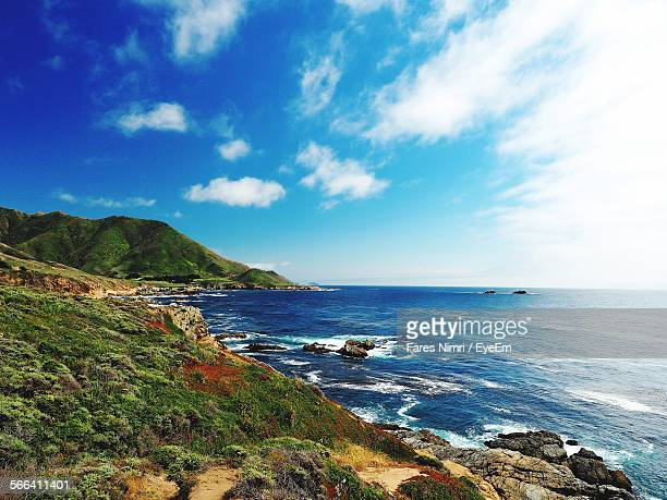 Scenic View Of Hill By Pacific Ocean Against Cloudy Sky