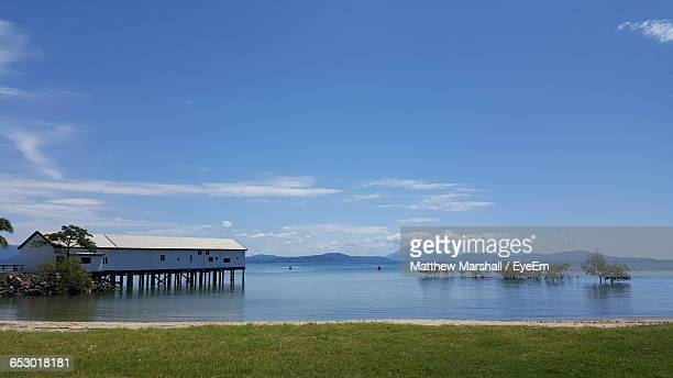 Scenic View Of Home By Lake Against Blue Sky