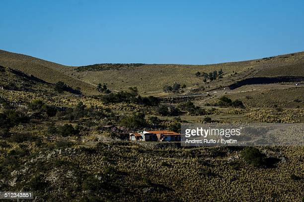 scenic view of house in mountains against clear blue sky - andres ruffo stock-fotos und bilder