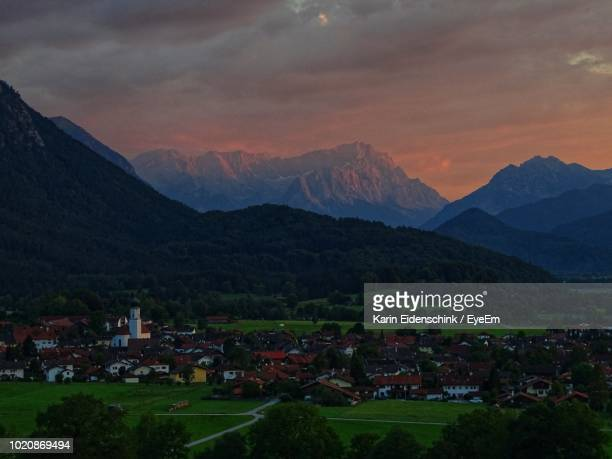 scenic view of houses and mountains against sky - karin eidenschink stock-fotos und bilder