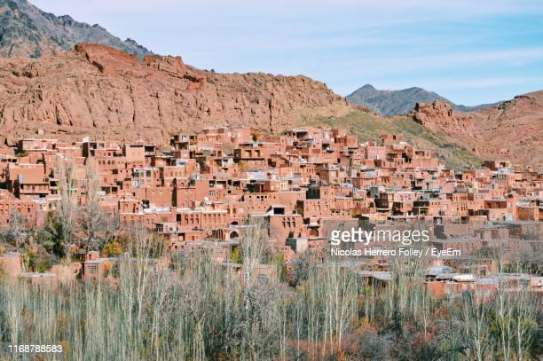 scenic view of houses and mountains against sky - isfahan stad stockfoto's en -beelden