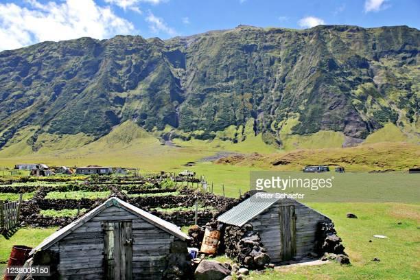 scenic view of houses and mountains against sky - isla tristán de acuña fotografías e imágenes de stock