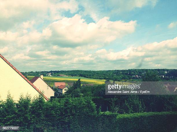 Scenic View Of Houses On Grassy Landscape