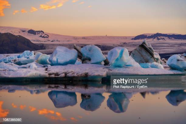 scenic view of icebergs and mountains on jokulsarlon glacial lagoon - naturwunder stock-fotos und bilder
