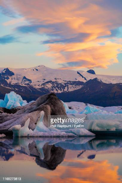 scenic view of icebergs in sea against snowcapped mountains and sky during sunset - jökulsárlón lagoon stock pictures, royalty-free photos & images