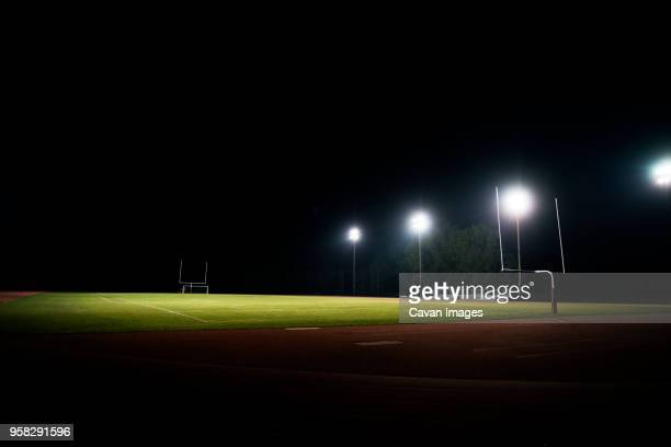 scenic view of illuminated american football field at night - high school football stock pictures, royalty-free photos & images