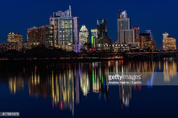 Scenic View Of Illuminated City By Lake At Dusk