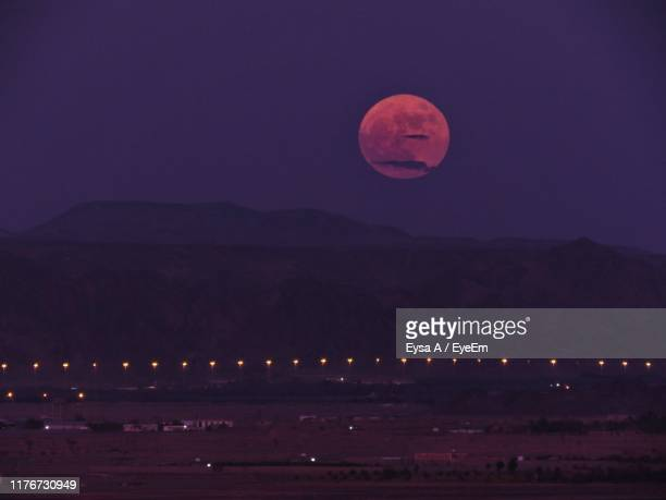 scenic view of illuminated mountains against sky at night - pink moon stock pictures, royalty-free photos & images