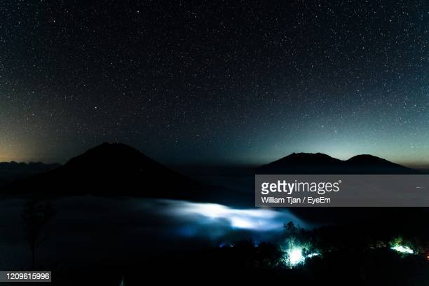 scenic view of illuminated mountains against sky at night - william moon stock pictures, royalty-free photos & images