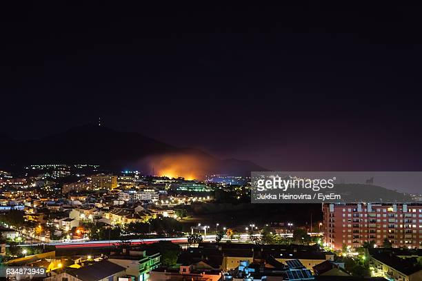 scenic view of illuminated residential district against sky at night - fuengirola stock photos and pictures