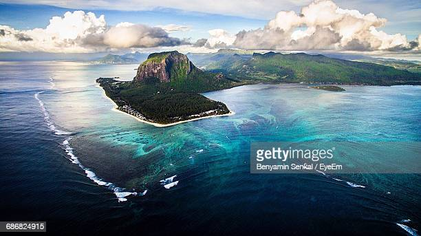 scenic view of island amidst sea against sky - insel mauritius stock-fotos und bilder