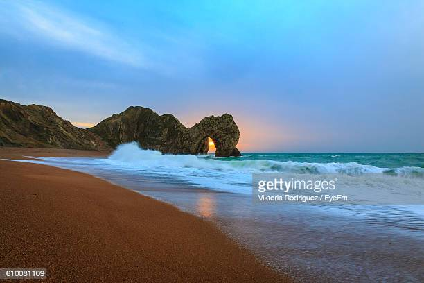 Scenic View Of Jurassic Coast Against Cloudy Sky During Sunset