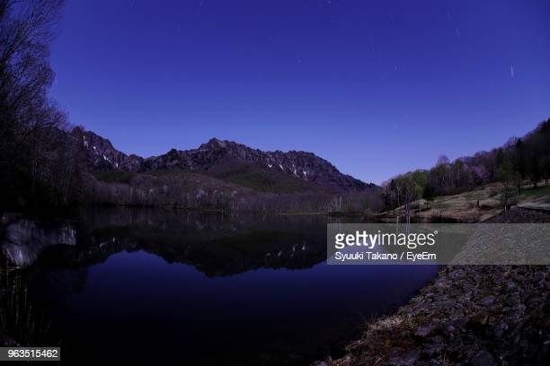 scenic view of lake against blue sky at night - land feature stock pictures, royalty-free photos & images