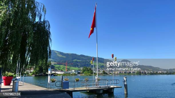 scenic view of lake against blue sky - schwyz stock pictures, royalty-free photos & images