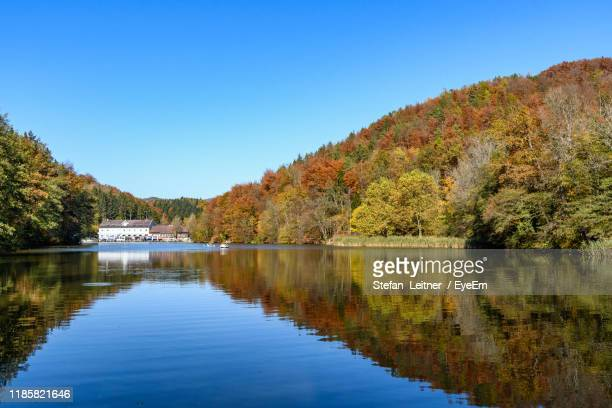 scenic view of lake against clear blue sky during autumn - thal austria stock-fotos und bilder