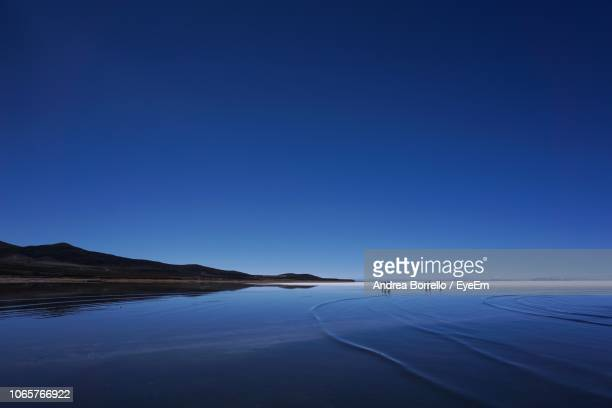 scenic view of lake against clear blue sky - salt flat stock pictures, royalty-free photos & images