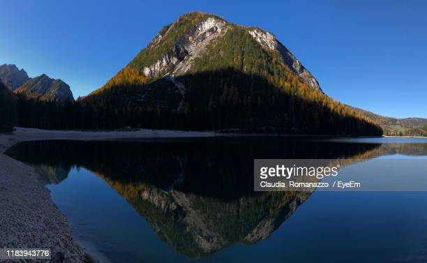 scenic view of lake against clear blue sky - claudia romanazzo foto e immagini stock