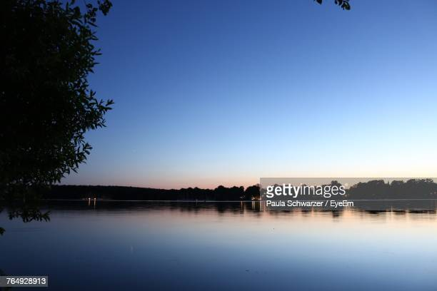scenic view of lake against clear blue sky - dämmerung stock-fotos und bilder