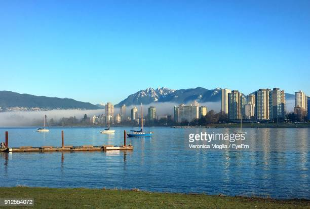 scenic view of lake against clear blue sky - english bay stock photos and pictures