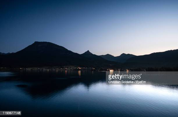 scenic view of lake against clear sky at dusk - christian soldatke stock pictures, royalty-free photos & images