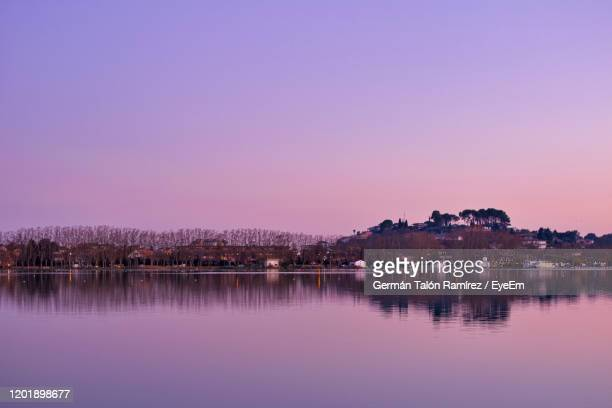 scenic view of lake against clear sky at sunset - banyoles stock pictures, royalty-free photos & images