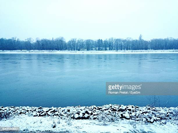 scenic view of lake against clear sky during winter - roman pretot stock-fotos und bilder
