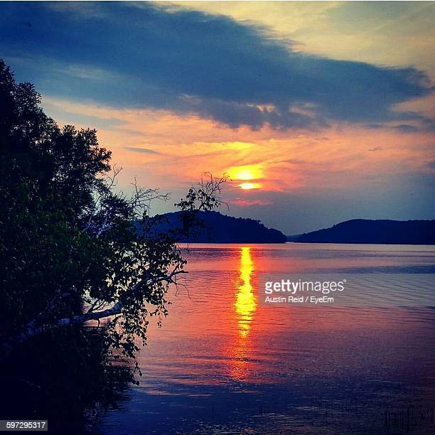 scenic view of lake against cloudy sky at sunset - reid,_wisconsin stock pictures, royalty-free photos & images