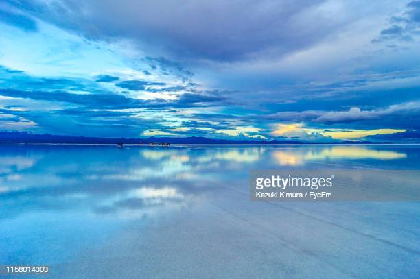 scenic view of lake against cloudy sky during sunset - ウユニ ストックフォトと画像