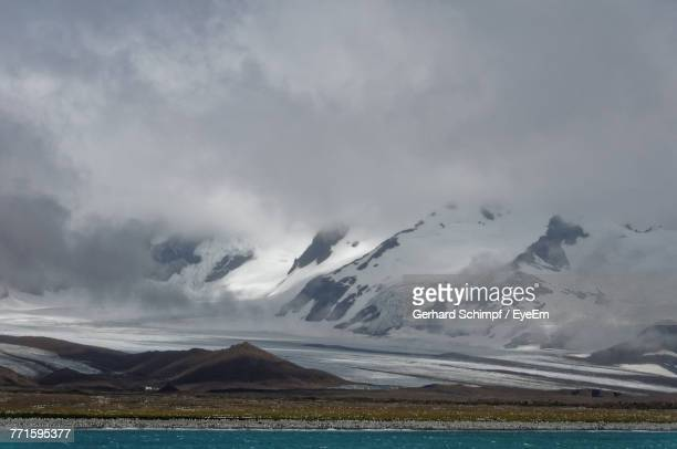 scenic view of lake against cloudy sky - gerhard schimpf stock pictures, royalty-free photos & images