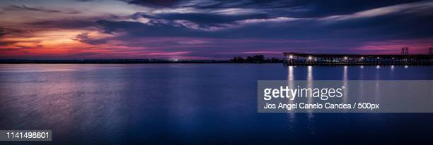 Scenic view of lake against dramatic sky at dawn