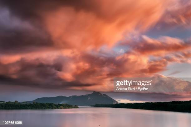 scenic view of lake against dramatic sky during sunset - andrea rizzi fotografías e imágenes de stock