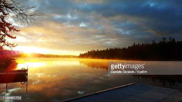 scenic view of lake against dramatic sky - winnipeg stock pictures, royalty-free photos & images