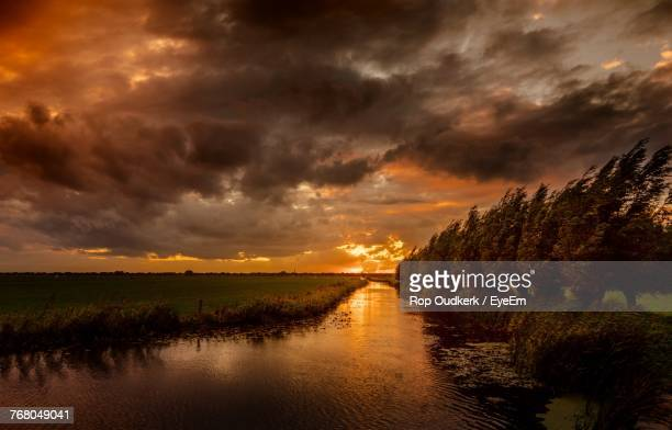 scenic view of lake against dramatic sky - almere stock pictures, royalty-free photos & images