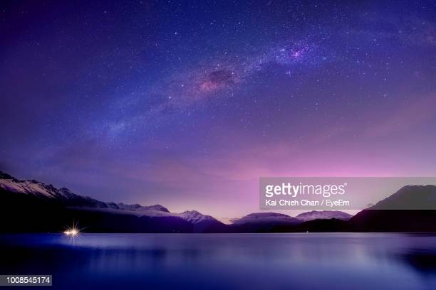 scenic view of lake against mountain at night - purple stock pictures, royalty-free photos & images