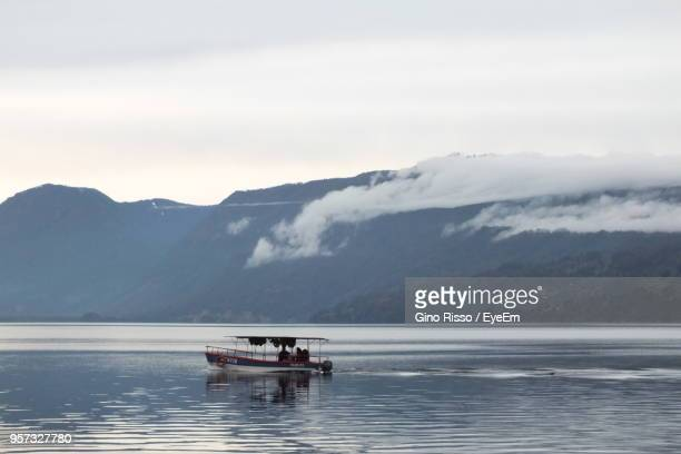 scenic view of lake against mountain range - villarrica stock photos and pictures