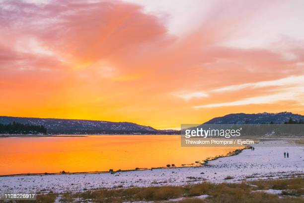 scenic view of lake against orange sky during sunset - big bear lake stock photos and pictures