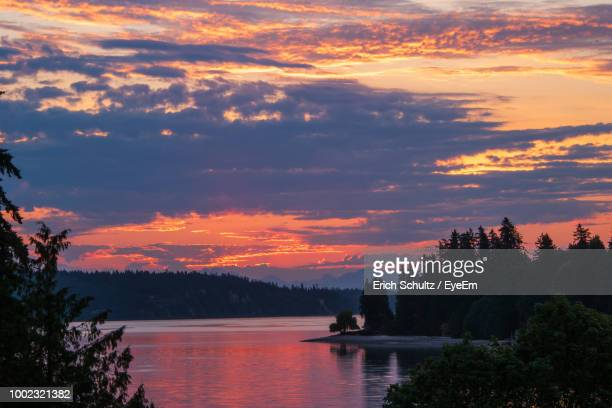 scenic view of lake against orange sky - kitsap county washington state stock pictures, royalty-free photos & images