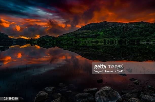 scenic view of lake against orange sky - vegard hanssen stock pictures, royalty-free photos & images