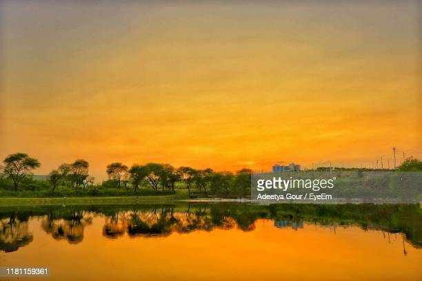 scenic view of lake against orange sky - madhya pradesh stock pictures, royalty-free photos & images