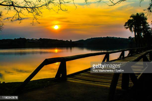 scenic view of lake against orange sky - curitiba stock pictures, royalty-free photos & images