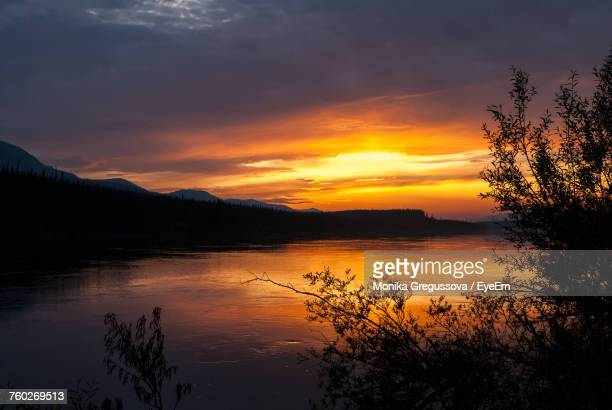scenic view of lake against orange sky - monika gregussova stock pictures, royalty-free photos & images