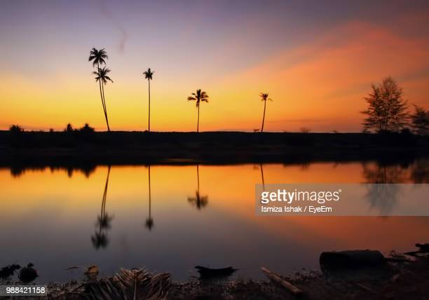 scenic view of lake against orange sky - terengganu stock pictures, royalty-free photos & images
